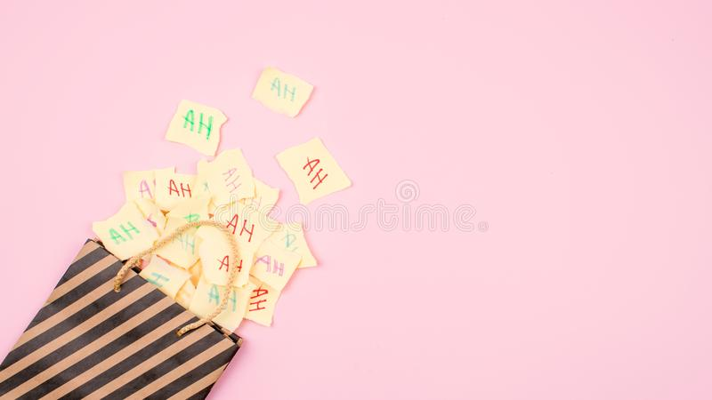 April Fools ' Day celebration background. Paper bag with many paper sheets with the words haha. 1 April mockup on pink background. royalty free stock photo