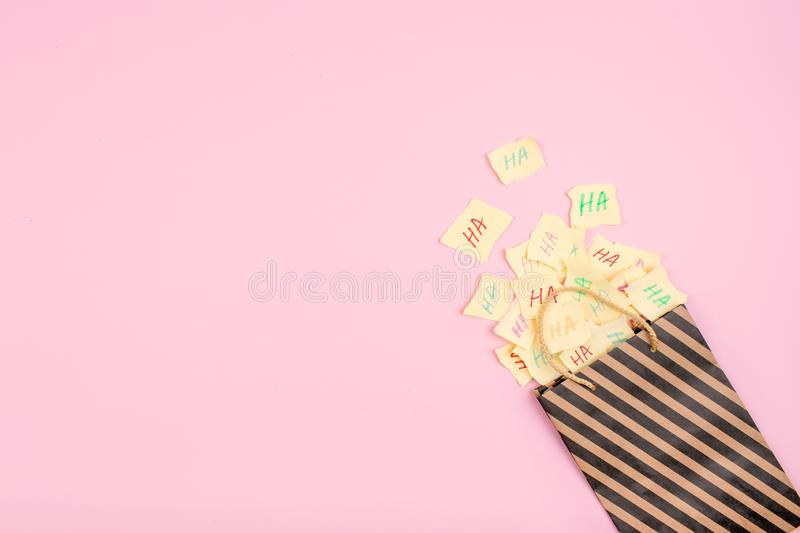 April Fools ' Day celebration background. Paper bag with many paper sheets with the words haha. 1 April mockup on pink background. royalty free stock photos