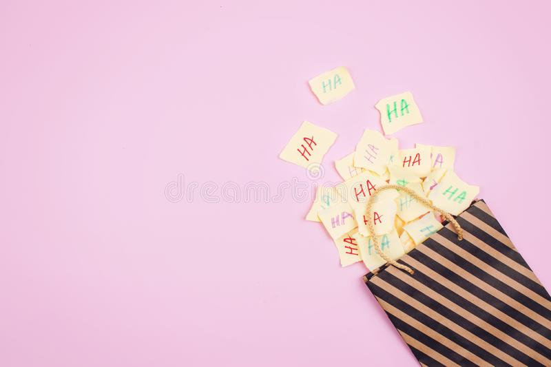 April Fools' Day celebration background. Paper bag with many paper sheets with the words haha. 1 April mockup on pink background. royalty free stock images