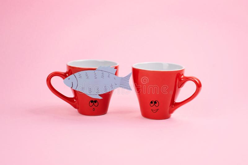 April Fools ' Day celebration, paper fish prank. Two joking laughing coffee cups with paper fish on pink background. All Fools ' D stock photo