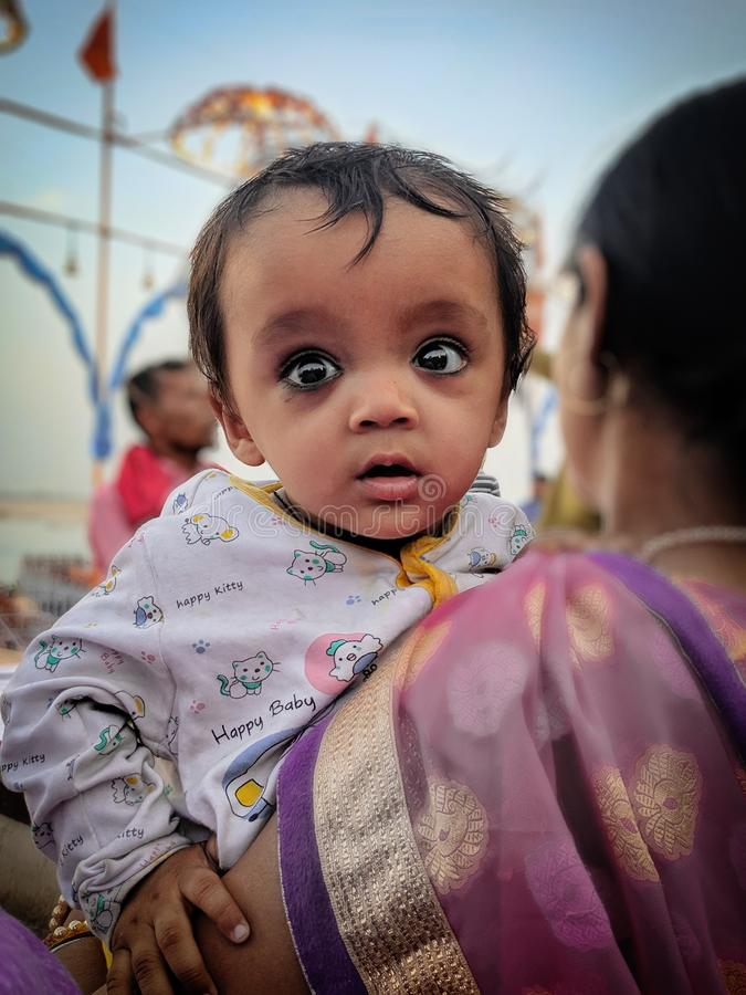 April 2019, Ghats van Varanasi, India Een moeder vervoert haar kind op haar overlapping terwijl het lopen naast Ghats van Varanas royalty-vrije stock foto's
