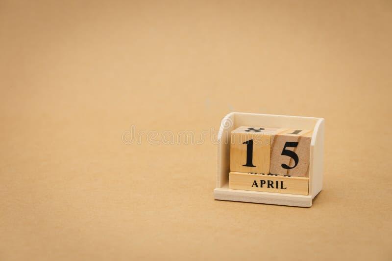 15. April: hölzerner Kalender auf hölzernem abstraktem Hintergrund der Weinlese Gesundheits-Tag mit als Hintergrunduniversaltagko lizenzfreies stockbild