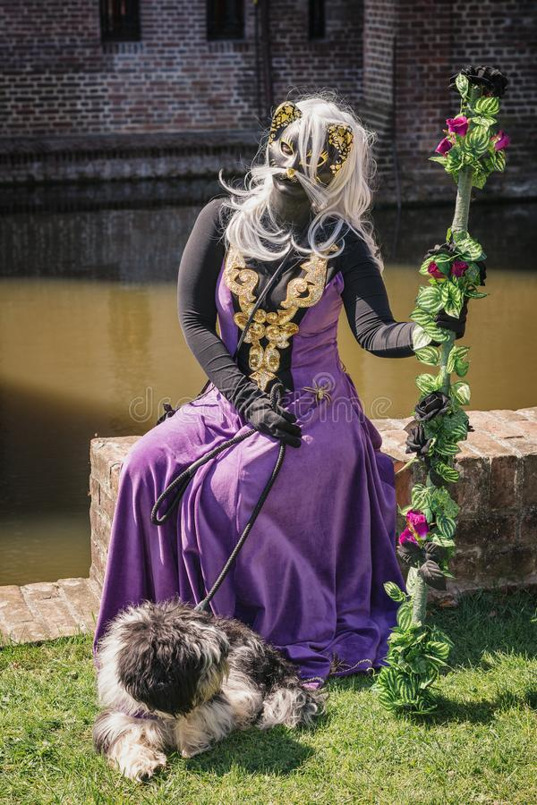 Catwoman with dog and staff sitting on a wall of the moat during royalty free stock photo