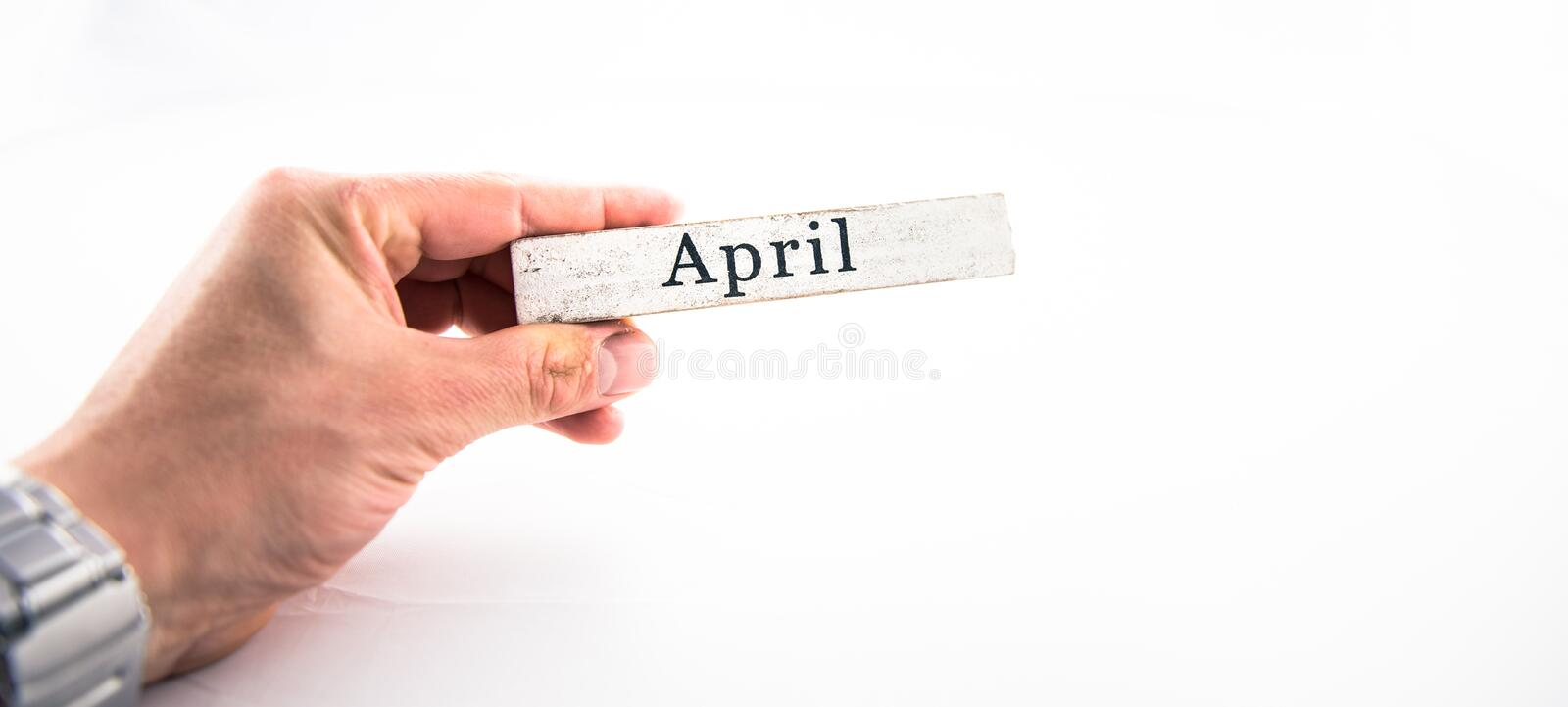 April - A hand holding calendar month block on white background royalty free stock images