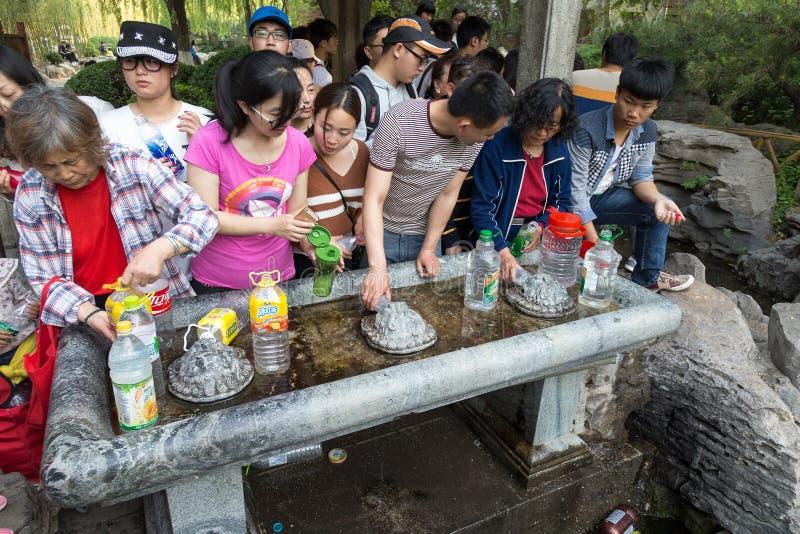 April 2015 - Jinan, China - plaatselijke bevolking die water van de lentes in beroemde Baotu Quan in Jinan, China nemen stock fotografie