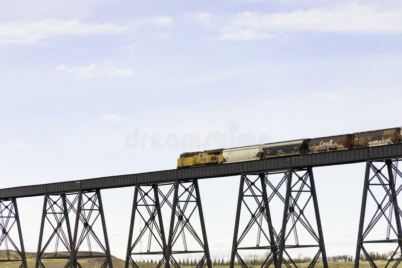 7 april 2019 - Lethbridge, Alberta Canada - Canadese Vreedzame Spoorwegtrein die de Brug kruisen Op hoog niveau royalty-vrije stock afbeelding