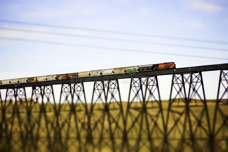 7 april 2019 - Lethbridge, Alberta Canada - Canadese Vreedzame Spoorwegtrein die de Brug kruisen Op hoog niveau stock foto