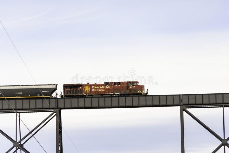 7. April 2019 - Lethbridge, Alberta Canada - kanadischer pazifischer Bahnzug, der die hochrangige Brücke kreuzt lizenzfreie stockfotografie