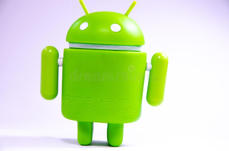 Green plastic Android figure on a white background and with a smartphone royalty free stock photo