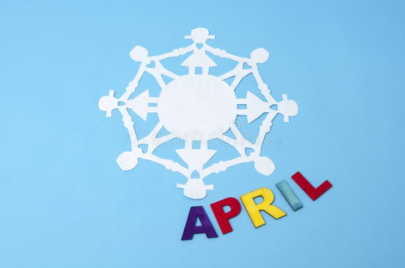 April made from colorful wooden letters and paper doll chain stock photography