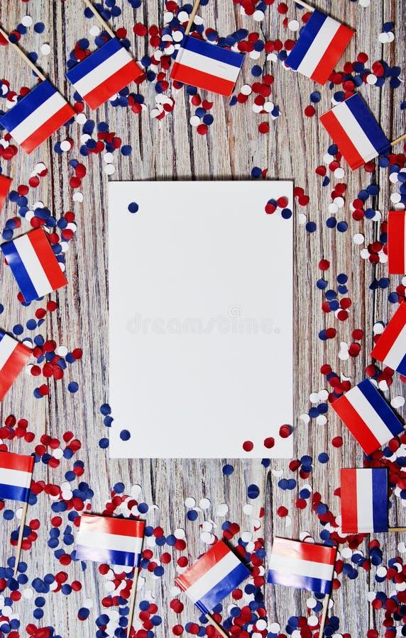 30. April Miniflaggen mit Papierkonfettis und Blättern des Weißbuches Das Konzept des niederländischen Unabhängigkeitstags und de stockfotografie