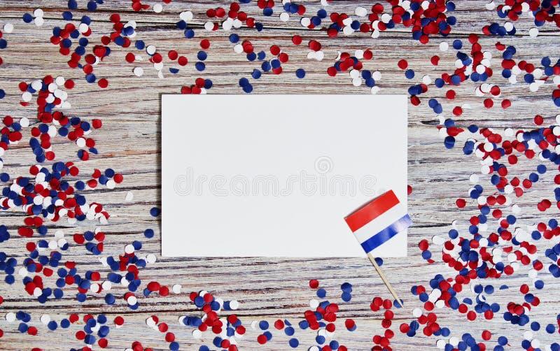 30. April Miniflaggen mit Papierkonfettis und Blättern des Weißbuches Das Konzept des niederländischen Unabhängigkeitstags und de stockbild