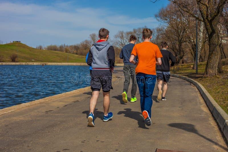 19 April, 2018 - Moskvastaden parkerar En grupp av ungdomarsom kör i sportswear royaltyfri bild