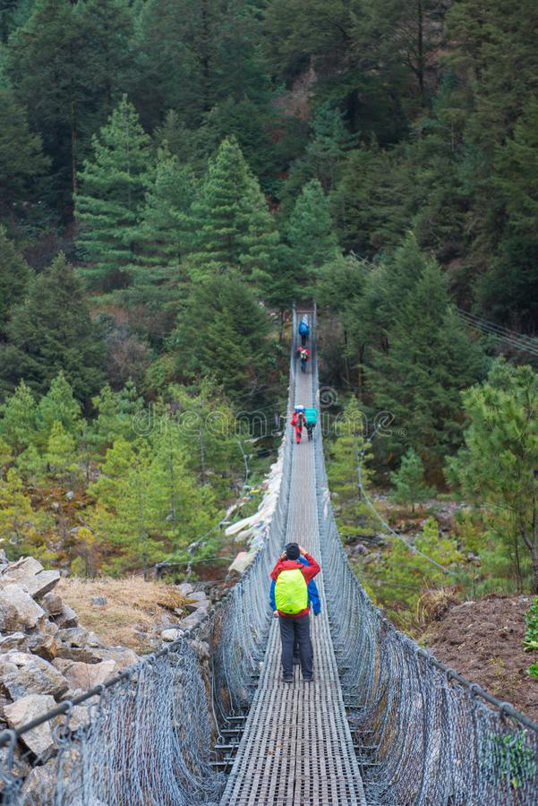 8 April 2018 - Nepal ::trekker cross the river by suspension bridge stock image