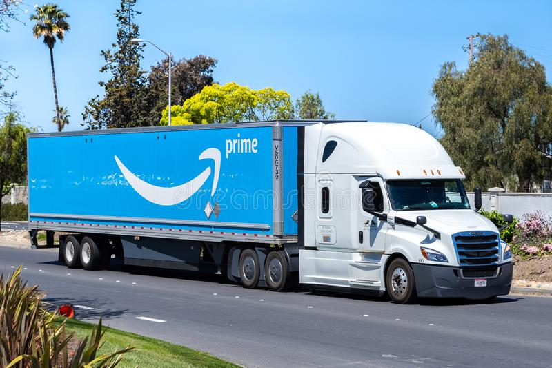 April 12, 2019 Newark / CA / USA - Amazon truck driving on a street in East San Francisco bay area; the large Prime logo printed. On the side stock photos