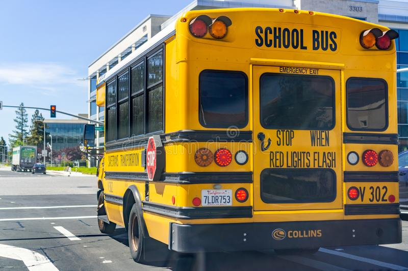 April 12, 2019 Santa Clara / CA / USA - School Bus waiting at a traffic junction in South San Francisco bay area stock photos