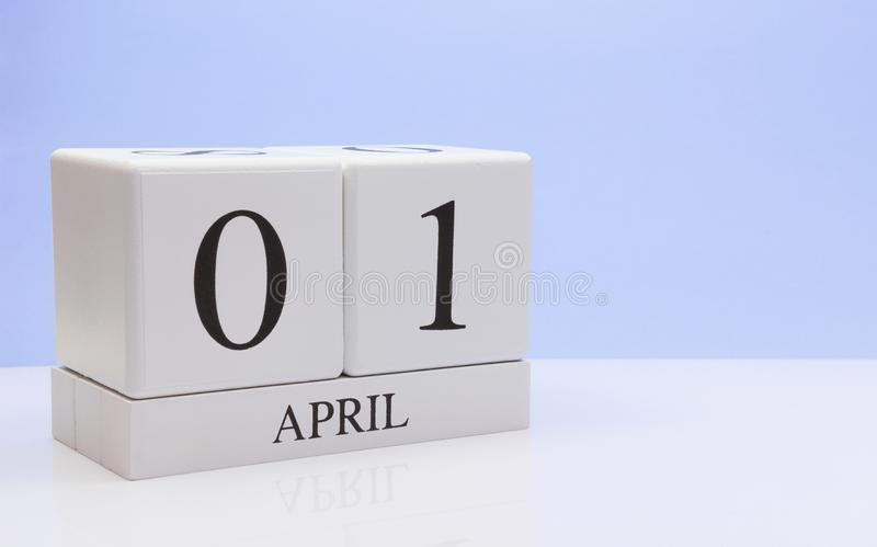 April 01st. Day 01 of month, daily calendar on white table with reflection, with light blue background. Spring time, empty space stock image
