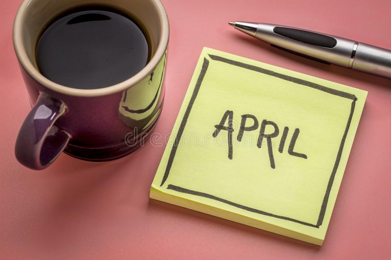 April on sticky note with coffee. April - handwriting in black ink on a sticky note with a cup of coffee royalty free stock photo