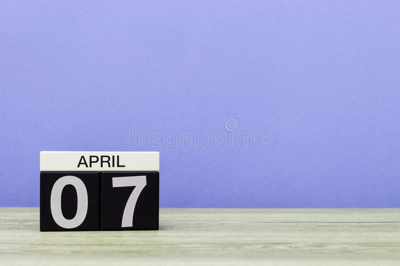April 7th. Day 7 of month, calendar on wooden table and purple background. Spring time, empty space for text.  stock photos