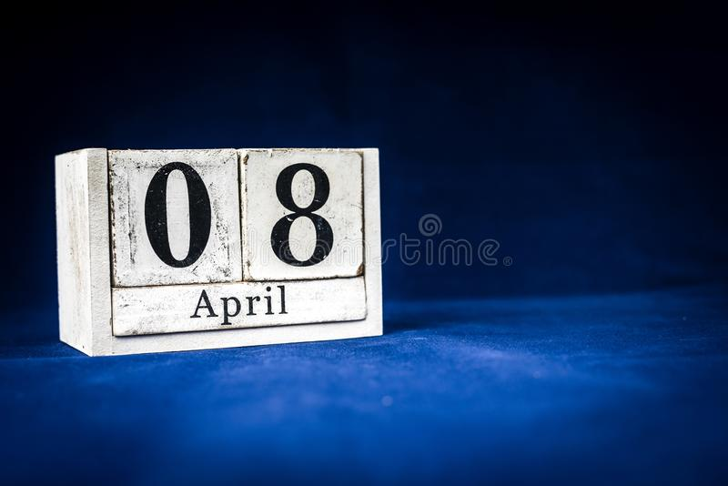 April 8th, Eighth of April, Day 8 of month April - rustic wooden white calendar blocks on dark blue background with empty space. For text royalty free stock image