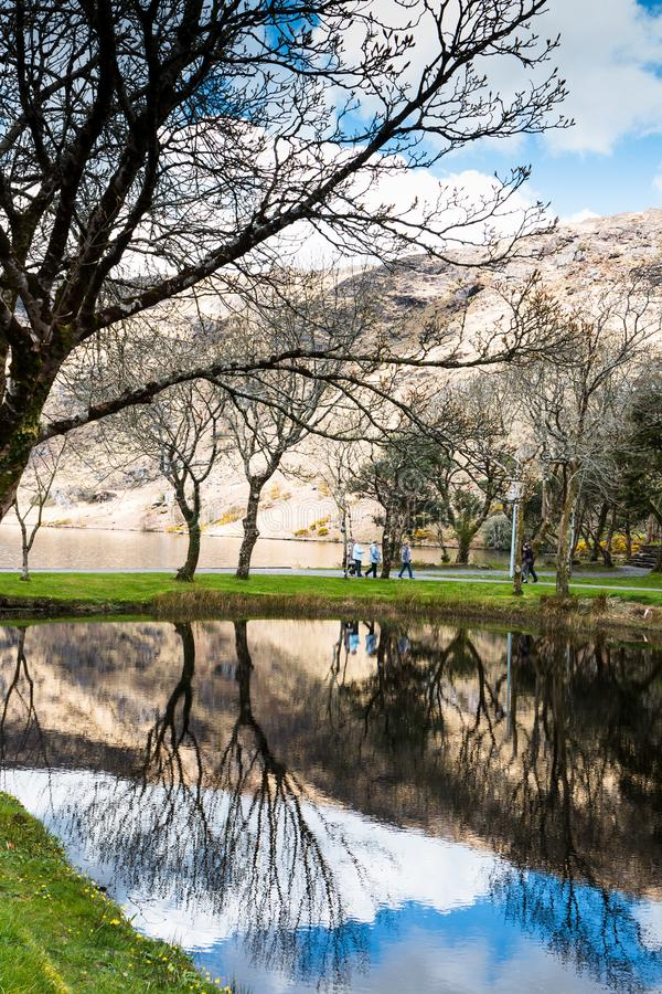 People walking towards Saint Finbarr`s Oratory, a chapel built on an island in Gougane Barra, a very serene and beautiful place. April 30th, 2018, Gougane Barra royalty free stock photos