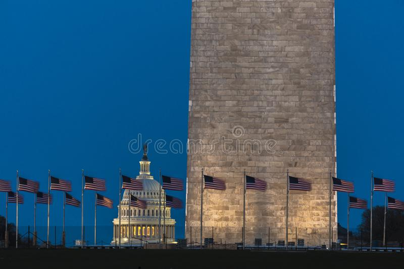 APRIL 8, 2018 WASHINGTON D.C. - US Flags with cropped view of US Capitol and Washington Monument. People, white stock image