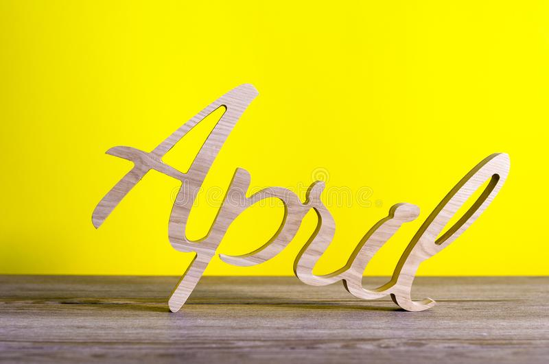 April - wooden carved word on yellow background. Spring time, 1st of april - Easter and fools day.  stock photos
