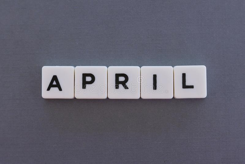 April word made of square letter word on grey background. Month time day date monthly calendar concept text spring reminder design number hello diary holiday stock photos