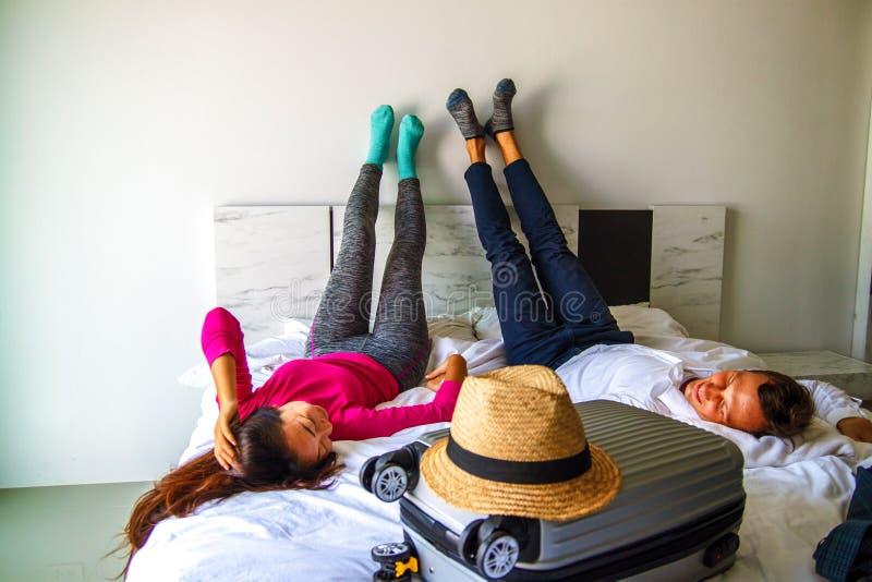 Apronte para aventuras Pares novos que preparam-se para a lua de mel, encontrando-se na cama com mala de viagem do curso imagens de stock