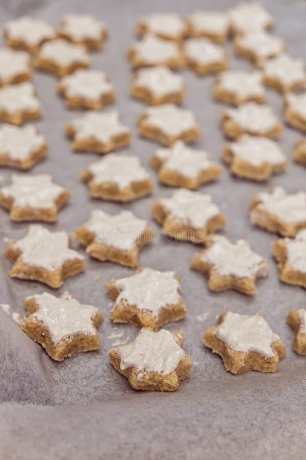 Apronte para cozer cookies do Natal da estrela da canela com vitrificação em vagabundos fotos de stock