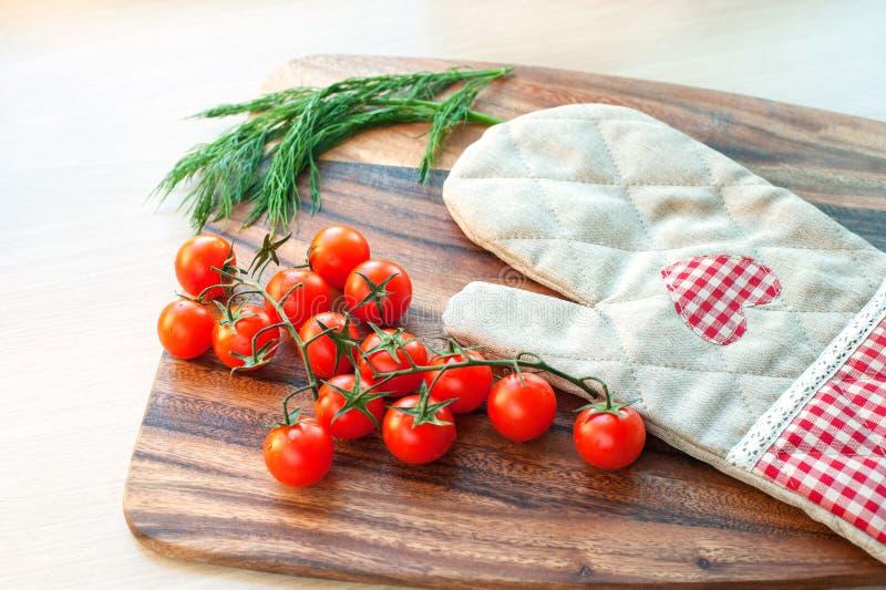 Apronte para cozinhar Vegetal-tomates e mitene do cozimento imagens de stock