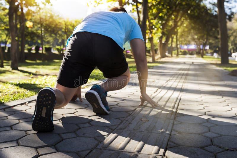 Apronte para ir! Feche acima da foto colhida do baixo ângulo da sapata do homem do atleta na pose do começo running imagens de stock