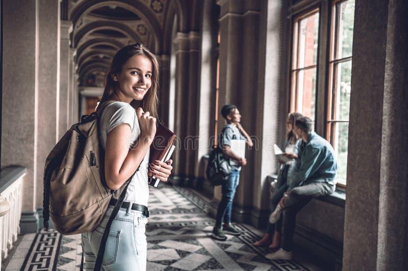 Apronte para o semestre novo! Mulher segura que guarda livros e que está no salão da universidade que olha a câmera foto de stock