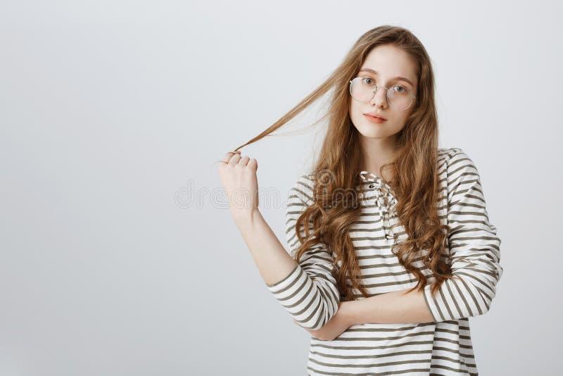 Apronte para ouvi-lo para fora e para ajudá-lo com sugestão Adolescente atrativo despreocupado que joga com cabelo e que olha foc imagens de stock royalty free