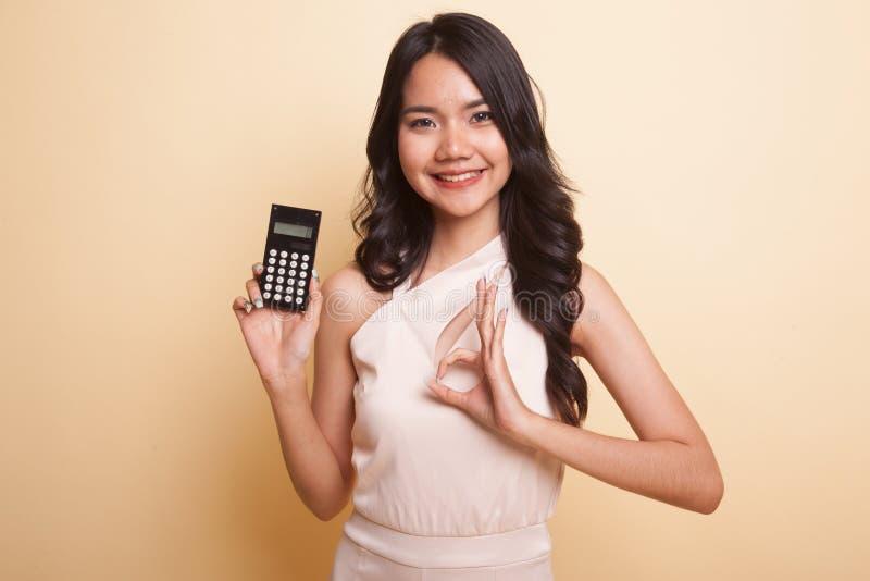 APROVAÇÃO asiática da mostra da mulher com calculadora imagens de stock royalty free