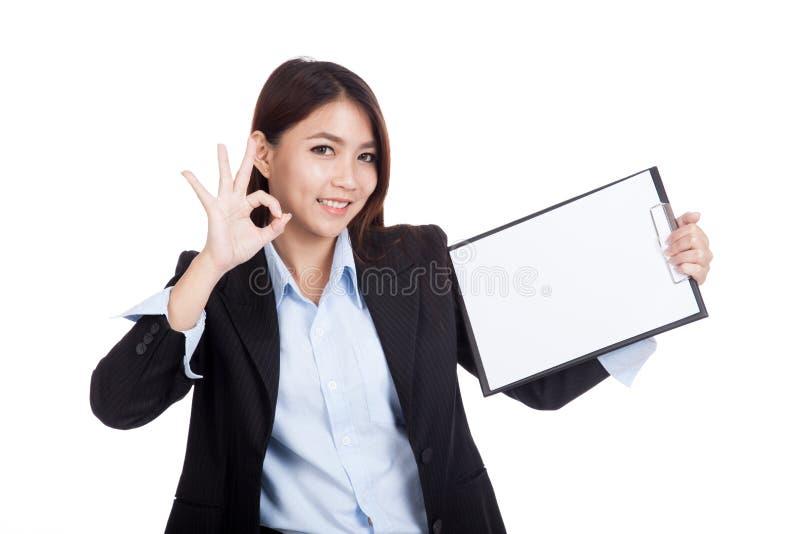 APROVAÇÃO asiática nova da mostra da mulher de negócios com prancheta imagens de stock royalty free