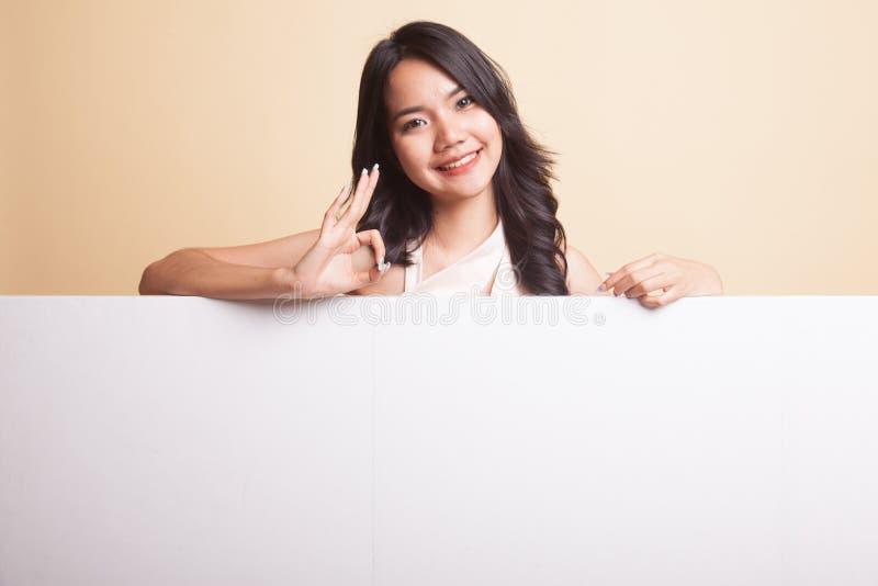 APROVAÇÃO asiática nova da mostra da mulher com sinal vazio imagens de stock