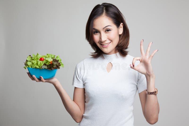 APROVAÇÃO asiática saudável da mostra da mulher com salada imagem de stock royalty free