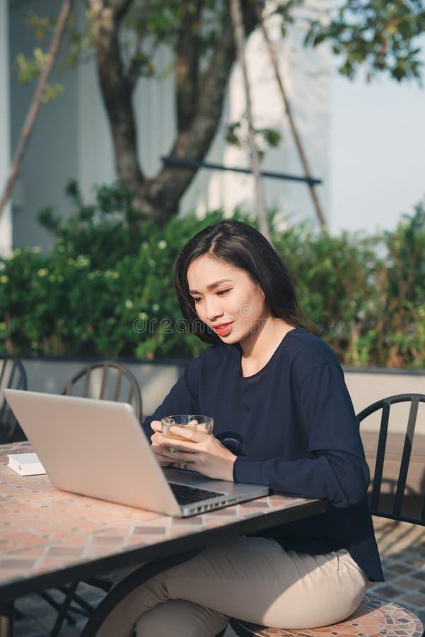 Aprovechar del Wi-Fi libre Mujer joven hermosa que trabaja o fotografía de archivo