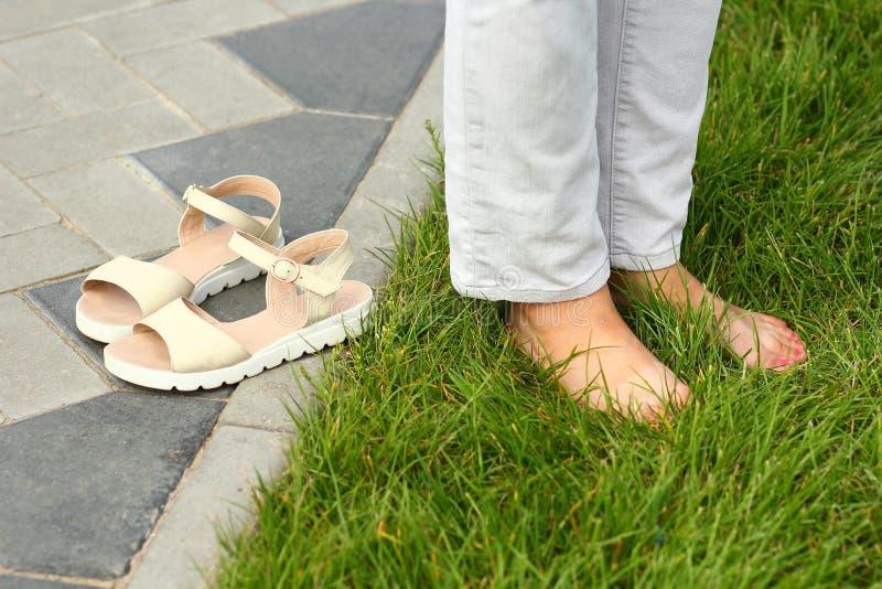 Aproximação dos pés nus das fêmeas na grama de verão, contrastando asfalto urbano fotos de stock