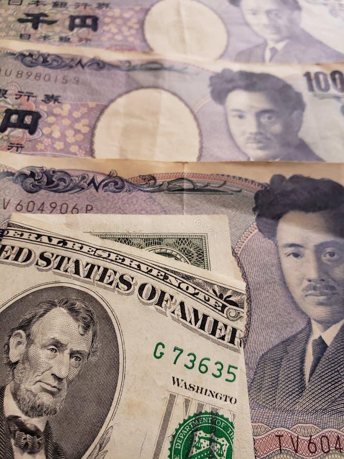 aproximação a uma cédula americana de cinco dólares e de cédulas japonesas de 1000 ienes imagens de stock royalty free