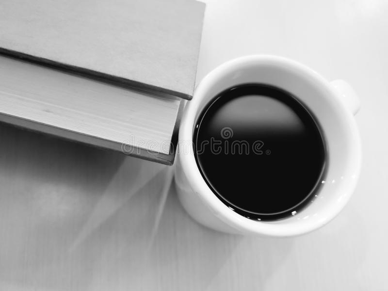 aproximação a uma xícara de café e o canto de um livro imagens de stock royalty free