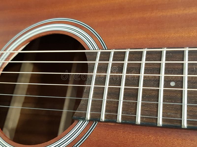 aproximando a caixa sadia de uma guitarra acústica, de um instrumento musical, de um fundo e de uma textura fotografia de stock