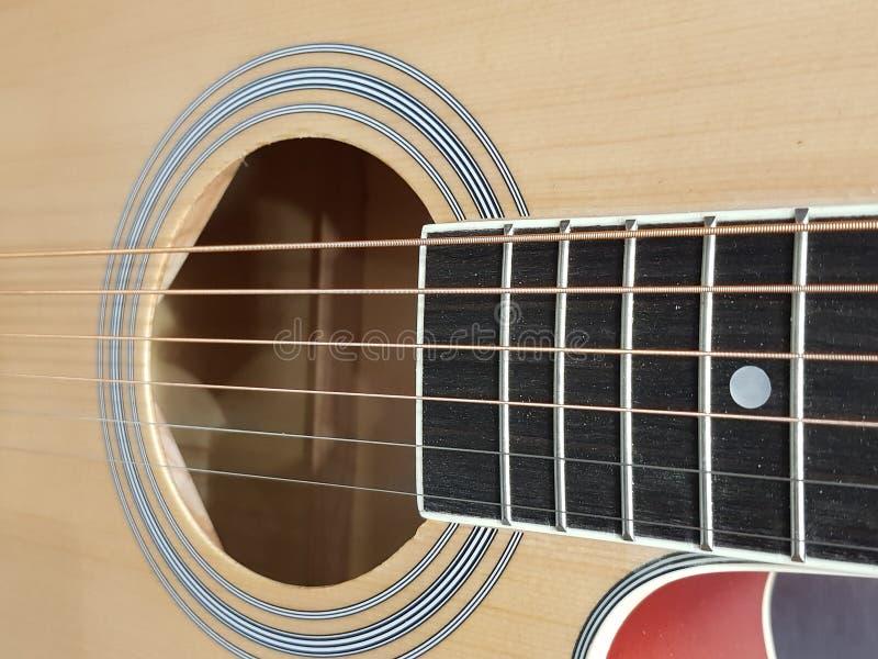 aproximando a caixa sadia de uma guitarra acústica, de um instrumento musical, de um fundo e de uma textura fotografia de stock royalty free