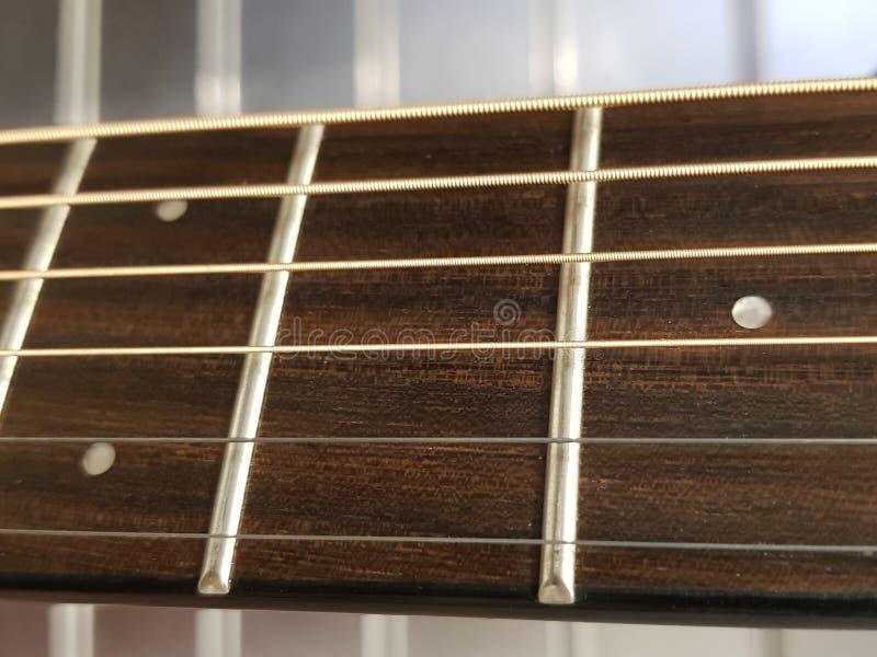 aproxime ao fingerboard de uma guitarra acústica, de um instrumento musical, de um fundo e de uma textura imagem de stock