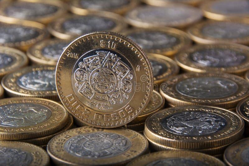 Aproxime a dez pesos mexicanos a moeda sobre mais moedas alinhadas e empilhadas, horizontal imagens de stock royalty free