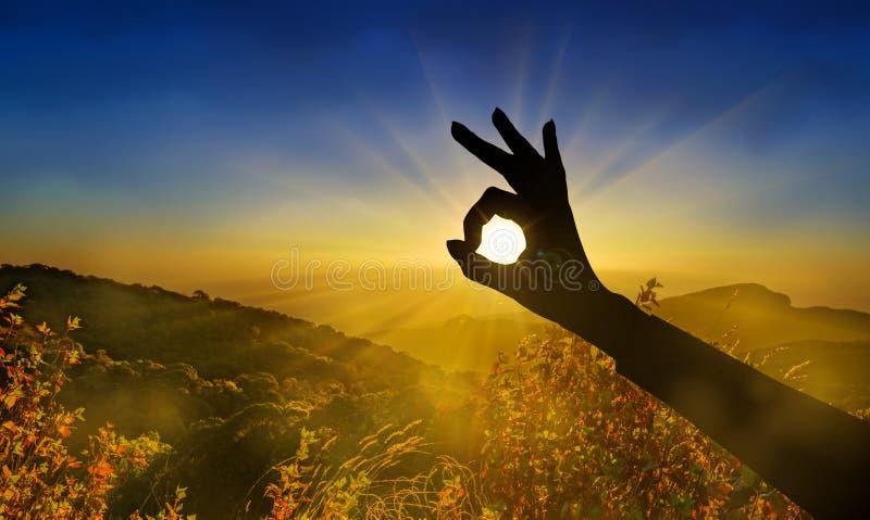 Apruebe la silueta de la muestra de la mano en la puesta del sol, salida del sol fotografía de archivo libre de regalías
