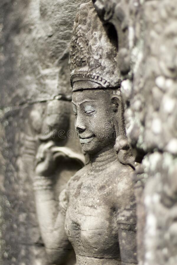 Apsara surrounded by intricate stone carving in Angkor Wat temple complex. Shallow depth of field image. Independent travel concept image royalty free stock photography