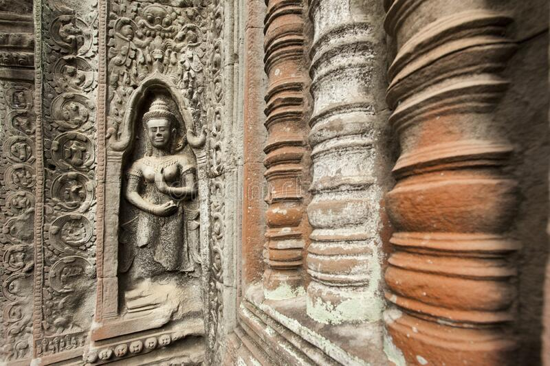 Apsara surrounded by intricate stone carving and pillars in Angkor Wat temple complex. Apsara surrounded by intricate stone carving in Angkor Wat temple complex stock photos