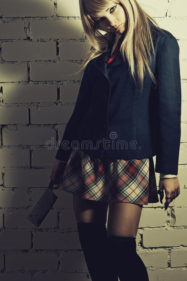 Apt pupil. Schoolgirl with cutter posing over brick wall stock photos